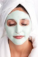Young woman having facial mask