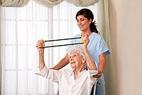 USA, Illinois, Metamora, Female nurse assisting senior woman on wheelchair using exercise band