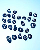 Stones with alphabets, spelling TRADE, blue background