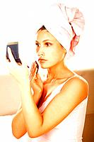 Pretty young brunette girl doing morning makeup. Girl has a towel on her head