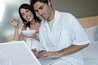 Mid adult man using a laptop with his wife holding a bowl and sitting beside him
