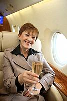Businesswoman with a glass of champagne in private jet