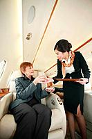Flight attendant serving businesswoman with a glass of water