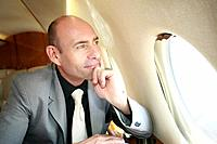 Businessman looking out of the window in a private jet