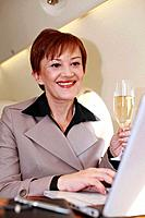 Businesswoman working on private jet while enjoying champagne