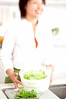 A young woman making salad