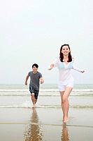 Man chasing woman on the beach