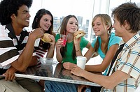 Close_up of two young men and three young women sitting in a restaurant and smiling