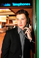 Businessman using public telephone at the airport
