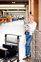 Woman reading a travel book with luggage cart in front of her