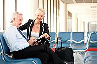 Businessman writing in organizer, businesswoman sitting beside him in airport lounge