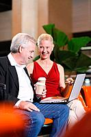 Businessman and businesswoman enjoying coffee in airport lounge