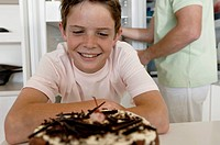 Close_up of a boy looking at a cake and smiling