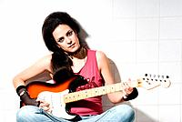 Punk female playing electric guitar on underground background.