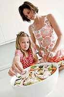 Mature woman cutting vegetables with her daughter picking a slice