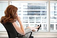 Woman sitting on chair in office and looking through window