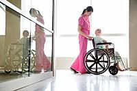 Nurse pushing girl on wheelchair in hospital corridor