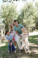 Mid adult couple and their two children playing with a dog in a park