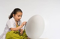 Girl examining a egg with a stethoscope