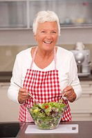 Elderly lady preparing salad