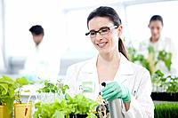 Female scientist watering plants in laboratory