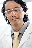 Portrait of smiling man wearing protective eyewear and laboratory coat