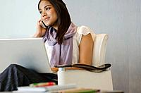 Businesswoman using laptop and cell phone
