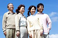 Portrait of young couple and their parents against a blue sky