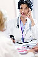 Mid adult doctor using cell phone at meeting