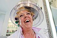 Smiling older woman in hairdryer