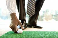 Businessman placing golf ball on artificial grass, low section