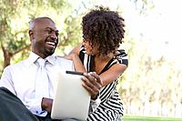 Laughing man and woman in park, man holding digital tablet