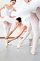 Ballet dancer adjusting colleague's pose