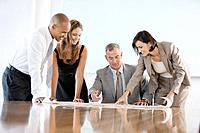 Two businessmen and two women in conference room