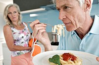 Senior man eating fettuccine with a senior woman holding an oven mitt in the background