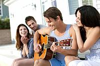 Friends sitting outside and playing guitar