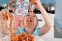 Close_up of a girl eating fettuccine with sauce around her mouth