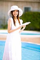 Young woman reading book poolside