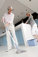 Low angle view of a senior man cleaning the floor with a senior woman standing beside him