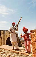 Man in traditional Rajasthani dress playing sarangi while a boy dancing, Jaipur, Rajasthan, India