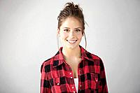 Studio portrait of smiling young woman in checked shirt