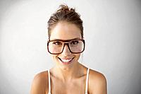 Studio portrait of smiling young woman wearing big glasses