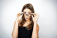 Studio portrait of beautiful woman wearing glasses and puckering