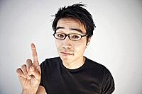 Studio portrait of young man wearing glasses and pointing with finger