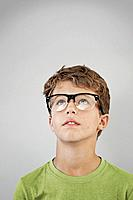 Portrait of boy 13_15 wearing glasses and looking up, studio shot
