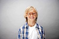 Portrait of boy 10_12 wearing glasses, studio shot