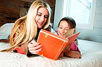Mother and daughter lying on bed reading book