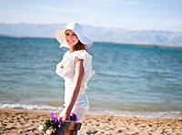 Bride carrying bouquet on beach