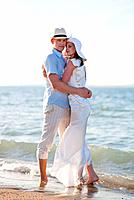 Newlywed couple embracing on beach