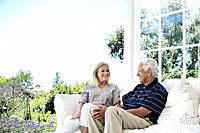 Smiling senior couple relaxing on porch